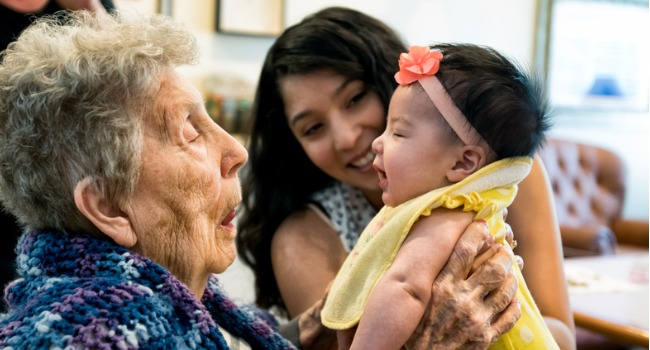 elderly-woman-holding-infant-granddaughter-as-mother-looks-on-smiling-picture-id541592296